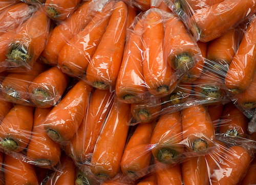 Group of fresh orange carrot in plastic bag sold at a market