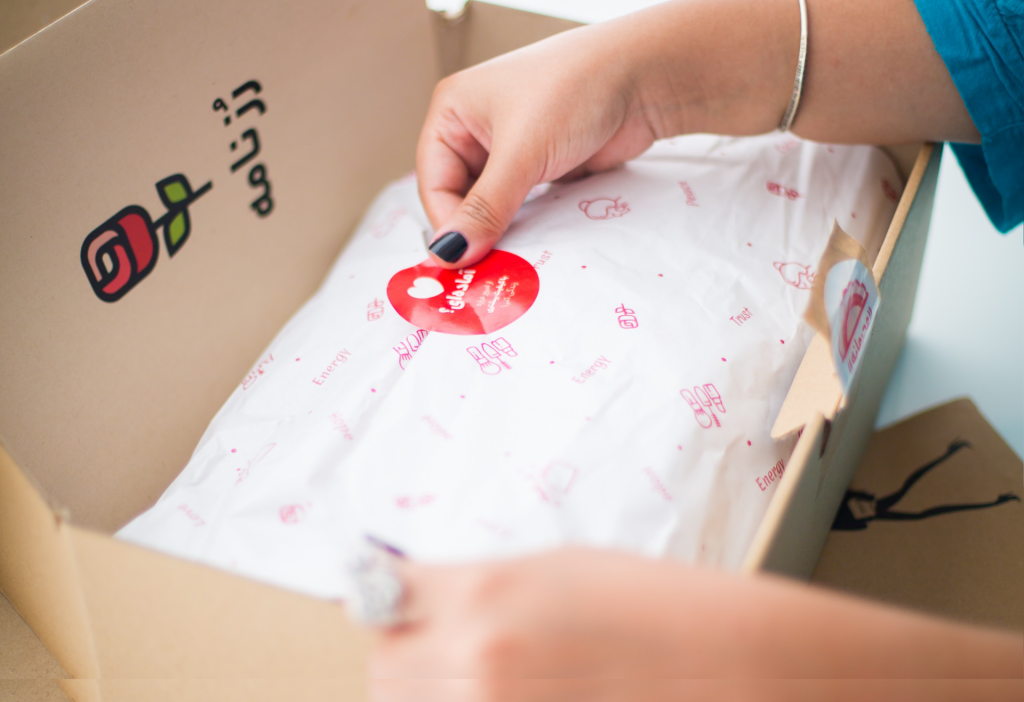 a person sealing a custom package with decorated tissue paper